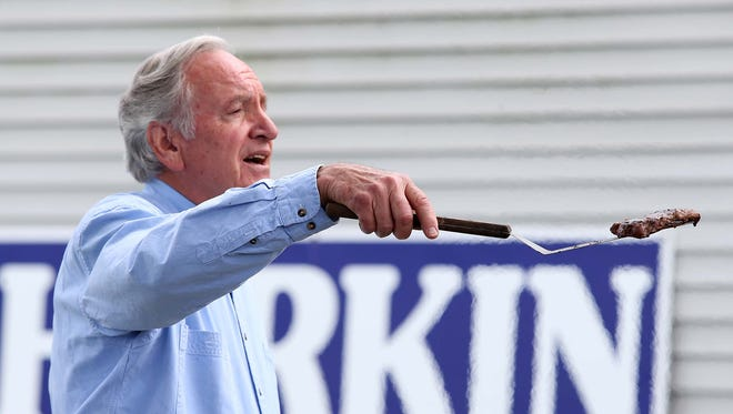 Sen. Tom Harkin shows members of the media a steak fresh off the grill during the annual Harkin Steak Fry on Sunday, Sept. 14, 2014, in Indianola, Iowa.