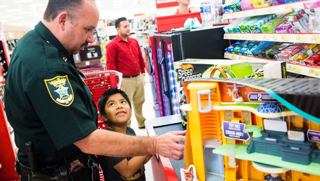 Captain Blake Lee waits in the checkout line with Kevin Simon, 6, during Shop with a Cop at Target in Coconut Point on Thursday, Dec. 22, 2016. Students participated in a Christmas essay contest and the winners were awarded the shopping spree.