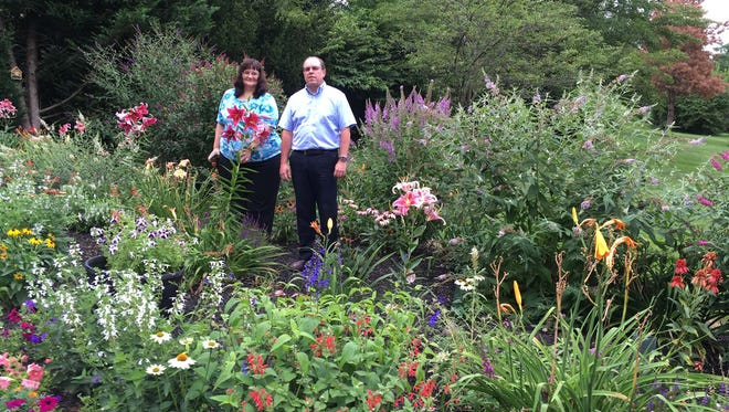 Stephanie and Craig Campbell stand in their eye-catching garden along Crescent Road in York Township.