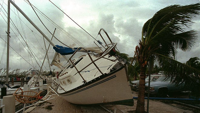 In this Aug. 24, 1992 file photo, a sailboat sits on a sidewalk at Dinner Key in Miami after it was washed ashore by Hurricane Andrew. Several days after it almost dissipated, Andrew rapidly strengthened and was a Category 4 storm at landfall in Homestead, Fla. The Hurricane Center measured a peak wind gust of 164 mph.