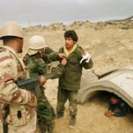 Iraqi troops emerge from heavily protected bunker to surrender to gun-toting Saudi soldiers during Operation Desert Storm in southeast Kuwait in this file photo from February 1991.