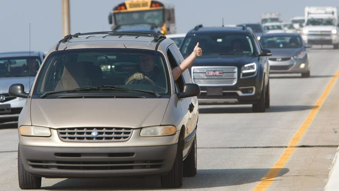 A driver gives a thumbs-up as traffic rolls onto the I-495 bridge as transportation officials reopen the southbound lanes July 31, 2014.