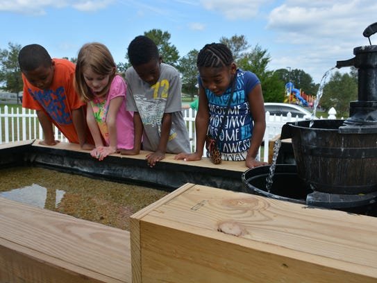 Students take a look inside the touch tank at the new
