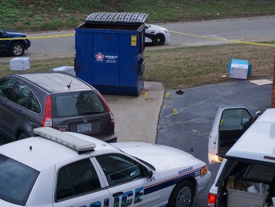 Several evidence markers are located near a blue Dumpster