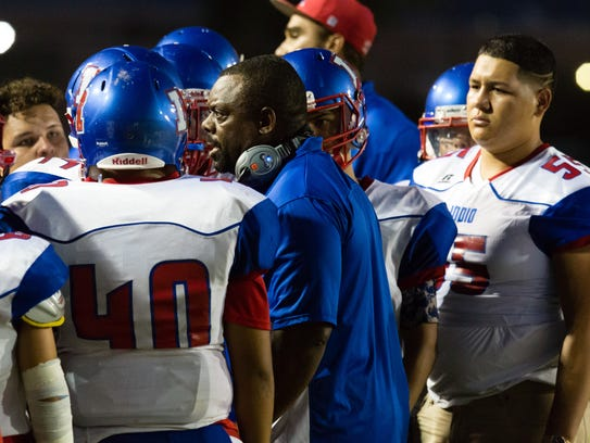 Indio football coach Martin White, talks to players during a game on Friday, August 26.
