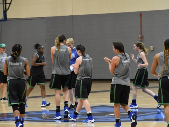 The UWF women's basketball team gathers around head