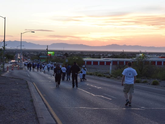 Marchers descend 10th Street as the sun sets on Saturday