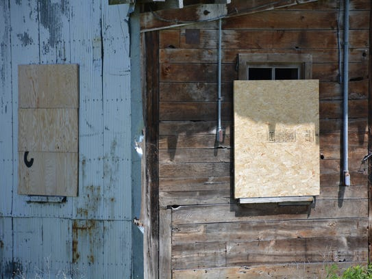 City workers added more boards to broken windows on