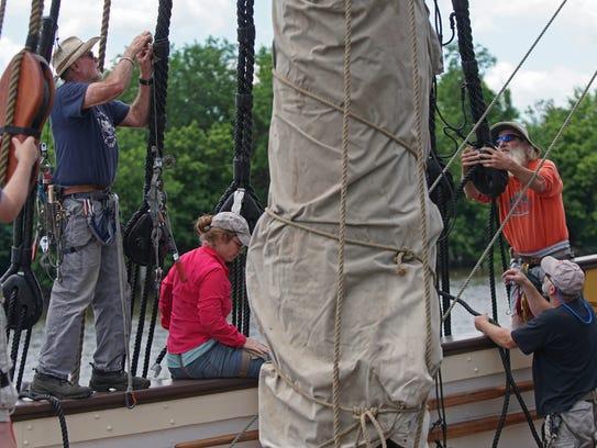 Crew members and volunteers help retie the Kalmar Nyckel