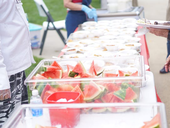 Volunteers serve watermelon at the ABCCM Veteran's