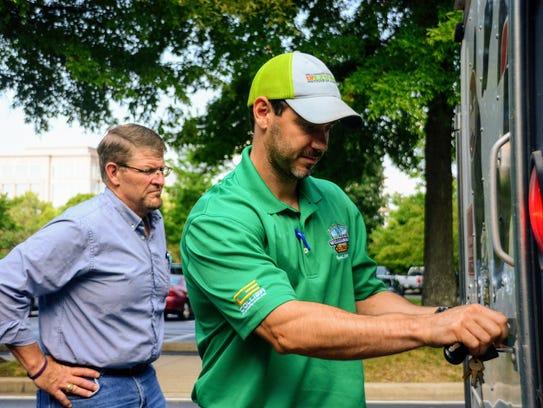 Matt Horsman, right, opens a trailer containing fiber