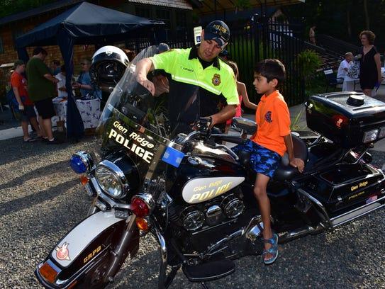 Avi Mehta sits on a Glen Ridge police motorcycle while