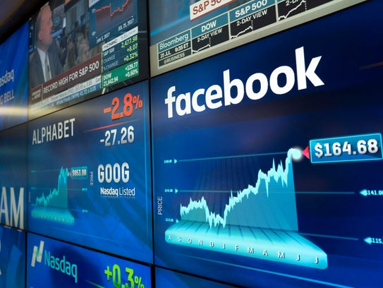 Alphabet and Facebook stock values are shown on a screen