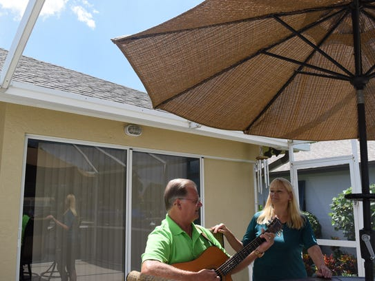 Jeff Hilt, 59, serenades his wife, Sharen, outside