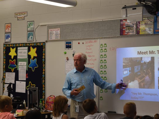 Granville Thompson talks to second-graders inside his