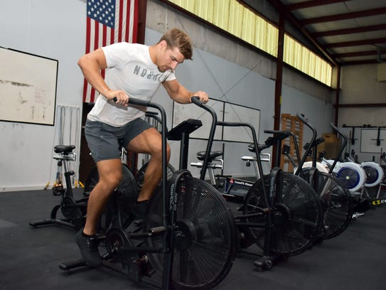 Alex Anderson works out on the bicycle at CrossFit
