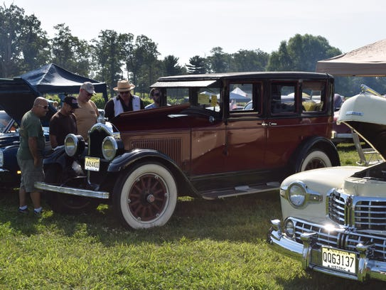 Spectators admire one of the many antique vehicles