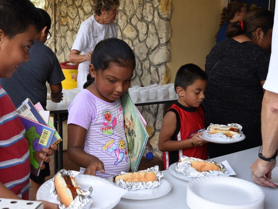 Children and their families grab food at Grace Place