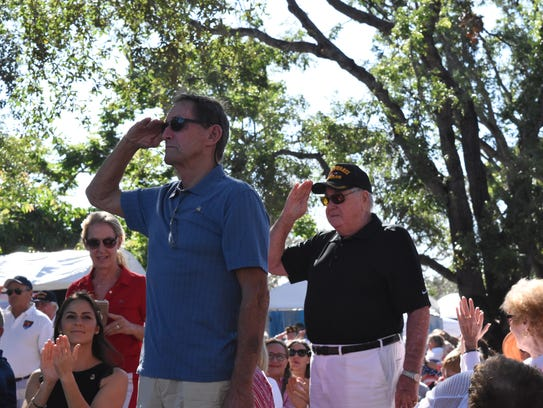 Two U.S. Navy veterans stand up as part of the Veterans