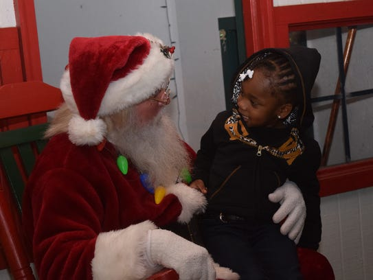 Nalah Gonzales, 3, meets with Santa Claus in downtown
