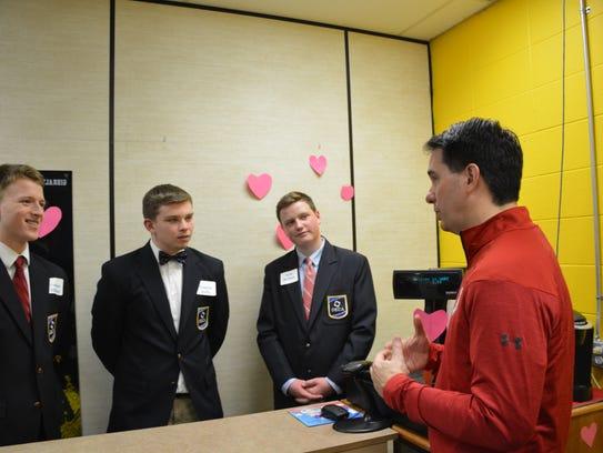 Gov. Scott Walker asks students Brandon Stillman, left,