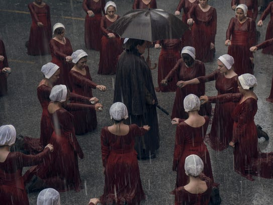 The handmaids, including Offred (Elisabeth Moss), surround