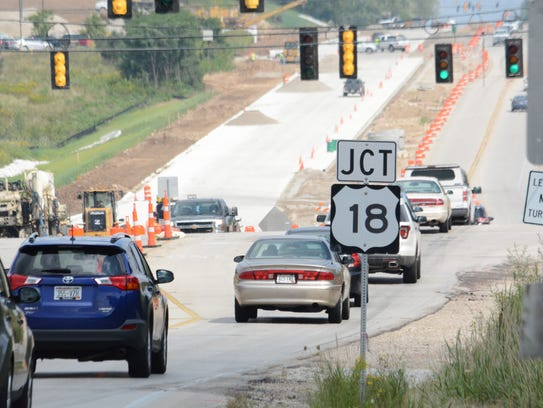 Traffic crosses Summit Avenue and heads into the construction
