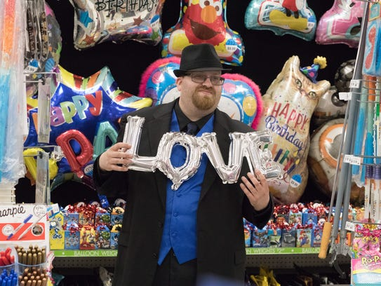 """Newlywed Justin Sietman poses with a """"love"""" balloon"""