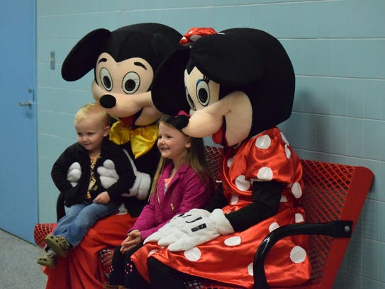 Alyson and Gunner Smith pose for a picture with Mickey