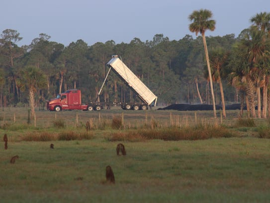 A truck dumps a load of biosolids shortly after 7 a.m.