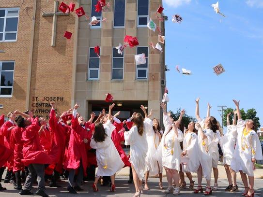 Graduates toss their caps Sunday after St. Joseph Central