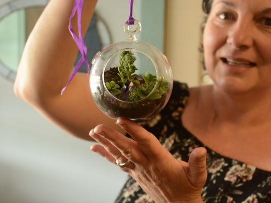 Solomon shows off one of her handmade terrariums that