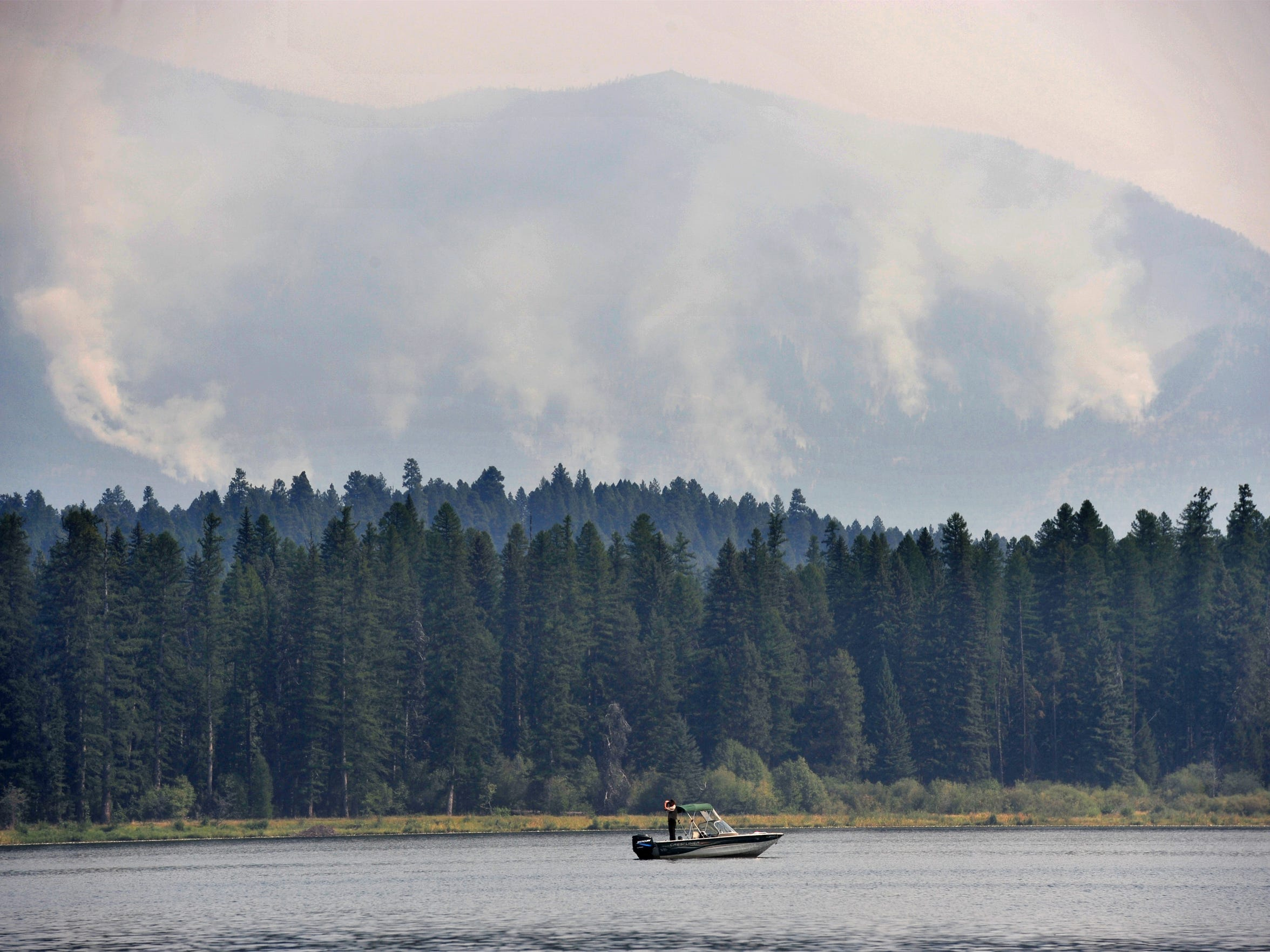 A law enforcement officer patrols Seeley Lake as fire fighting helicopters fill their water tanks to battle the Rice Ridge Fire on Friday.
