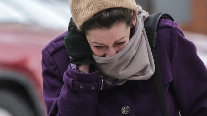 Anne Cucchiara of Washington Township shields her face from the freezing temperatures and high winds while walking on Washington Blvd. in downtown Detroit in January.