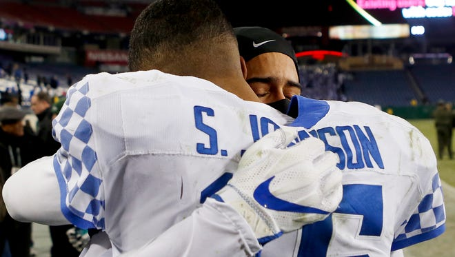 Kentucky's Stephen Johnson hugs fellow senior Kendall Randolph after the Cats lost to Northwestern in the Music City Bowl.