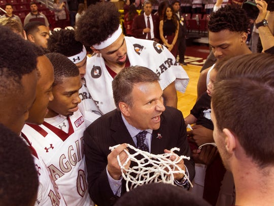 New Mexico State basketball head coach Chris Jans tells his team that they have achieved one of their goals, as he celebrates with the Pan American Center net he cut down Saturday night.