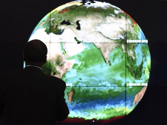A conference attendee looks at a projection of Earth