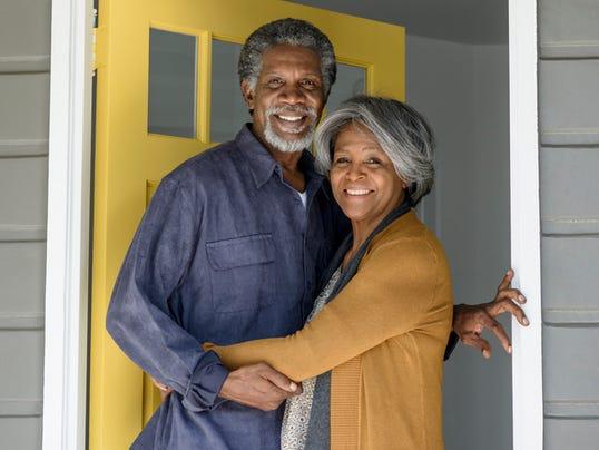 Senior African American couple in doorway, embracing