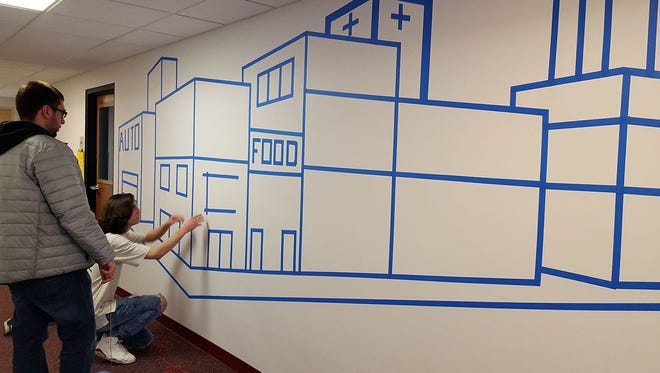 Introduction to Drawing students create artscapes on the UW-Sheboygan campus using painters' tape.
