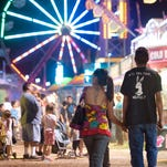 Johnny Souza, right, and his fiancée Corina Mendoza of Tulare walk along the midway of the Tulare County Fair on Thursday .