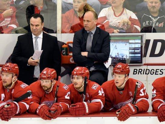 Red Wings head coach Jeff Blashill, center background, watches his team play against the Senators during the first period Monday at Joe Louis Arena.