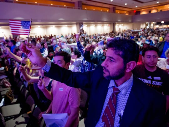 "Mohammed Al Foazi, originally of Iraq but now residing in Mesa, waves a flag during a naturalization ceremony at Mesa's Celebration of Freedom.  ""I'm very excited for all of this,"" Al Foazi said. ""I've been waiting for this for a long time."""