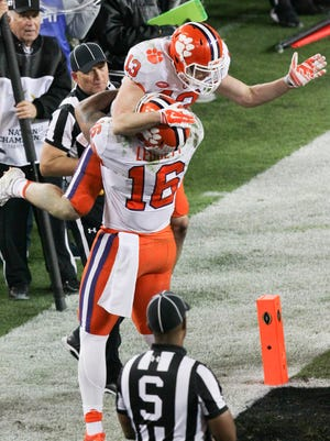 Clemson wide receiver Hunter Renfrow (13) is lifted by tight end Jordan Leggett (16) after catching the winning touchdown from quarterback Deshaun Watson (4) against Alabama during the fourth quarter of the National Championship game on Monday at Raymond James Stadium in Tampa, Florida.