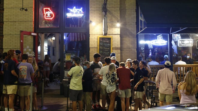 People wait to get into a bar in downtown Athens, Ga, on Friday, June 5, 2020.