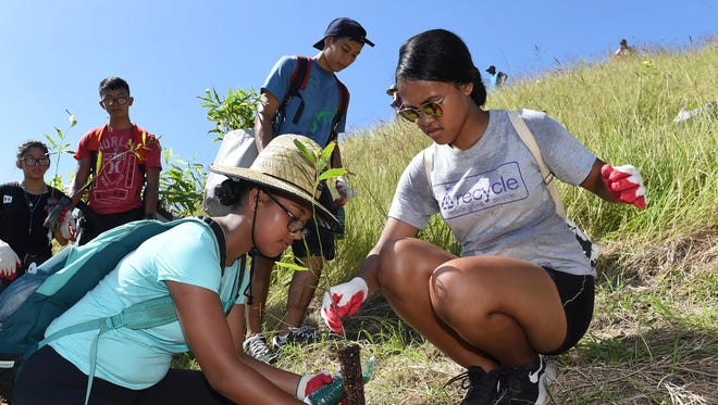 George Washington High School students Cindy Frederick, 16, right, and Jiann Ludwig, 15, participate in The Manell Watershed Reforestation Planting Event in Merizo on Oct. 21, 2017.