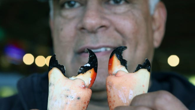 Walter Flores holds a pair stone crab claws at Golden Rule on Dec. 12, 2017 in Palmetto Bay, Fla. There is a shortage of the crabs, driving up prices.