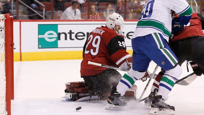 Vancouver Canucks' Brendan Gaunce (50) deflects the puck past Arizona Coyotes' Anders Lindback (29), of Sweden, for a goal during the first period of an NHL hockey game Friday, Oct. 30, 2015, in Glendale, Ariz.