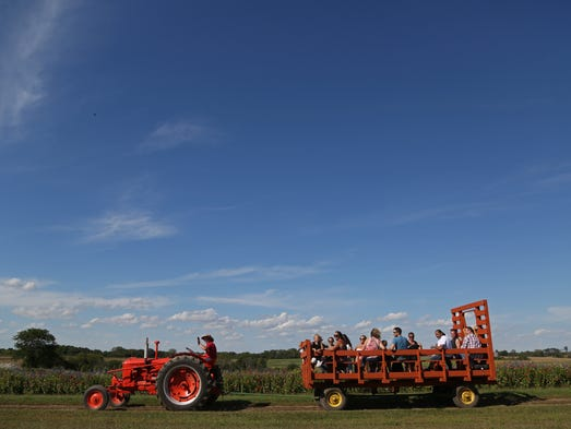 Visitors to Howell's Pumpkin Patch take a hayrack ride