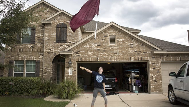 Dripping Springs High School senior Jaden Gardner, 17, tosses a flag into the air Thursday in the driveway of their family home during a virtual color guard practice.