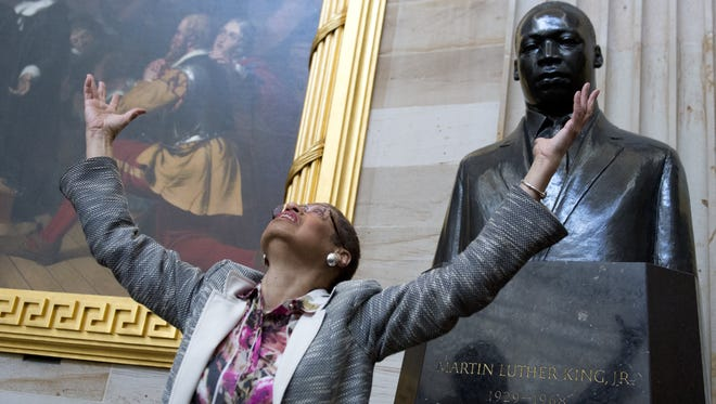 US Congressional Delegate Eleanor Holmes Norton of Washington, DC, looks up at the ceiling as she speaks with students about Black History Month alongside a statue of Martin Luther King, Jr., during a tour of the Rotunda at the US Capitol in Washington, DC, on February 20, 2014.